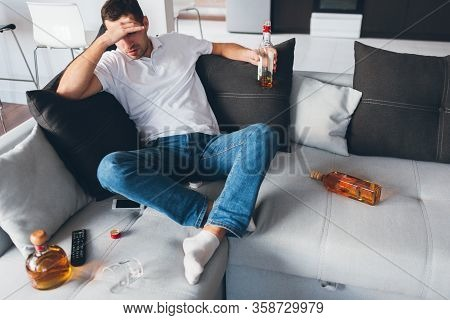 Young Man Watch Tv In His Own Apartment. Alcoholic Sit On Sofa Amoing Opened Bottles With Whiskey. S