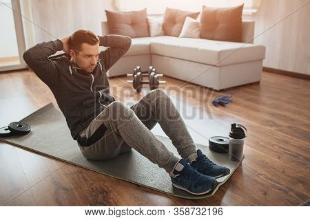 Young Ordinary Man Go In For Sport At Home. Hardworking Freshman Sit On Mat And Do Abs Excercise. No