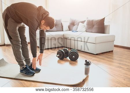 Young Ordinary Man Go In For Sport At Home. Stand On Mat And Stretch Down To Toes. Ordinary Guy Warm