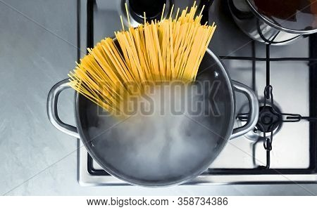 Cooking Raw Spaghetti In The Boiling Water Contained In A Saucepan. Italian Cuisine. Raw Food. Inter