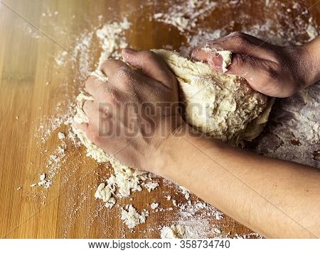 Female Hand Kneading A Flour Dough By Rolling It On A Wooden Board. Preparation Of Flour-based Food