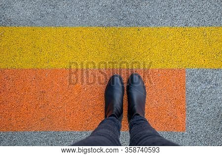 Black Shoes Standing On The Asphalt Concrete Floor With Yellow And Orange Lines. Feet Shoes Walking