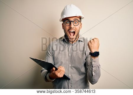 Young architect inspector man wearing builder safety helmet and using clipboard screaming proud and celebrating victory and success very excited, cheering emotion