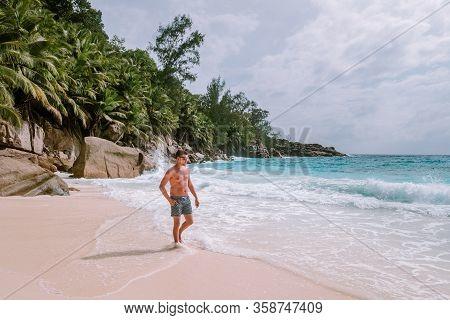 Young Men In Swim Short Tropical Beach Seychelles Mahe, Petite Anse Tropical Beach Seychelles