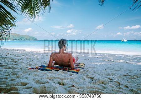Cote Dor Beach, Praslin Seychelles Tropical Island, Young Men In Swim Short On The White Beach With
