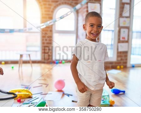 Adorable african american toddler smiling happy. Standing with smile on face playing around lots of toys at kindergarten
