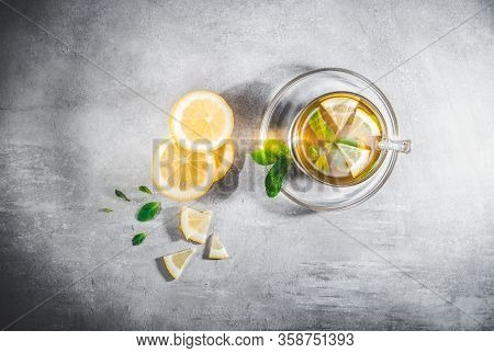 Mint Tea Leaves In A Cup With Fresh Slice Lemon On Gray Table. Topview, Above