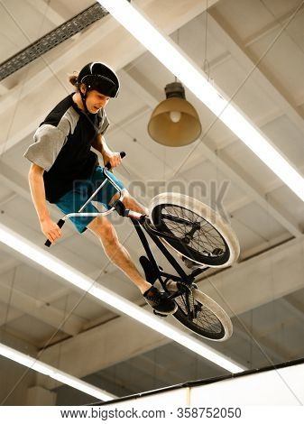 Young BMX Rider Doing Extreme Tricks on the Bike in the Skatepark Indoor. Healthy and Active Lifestyle.