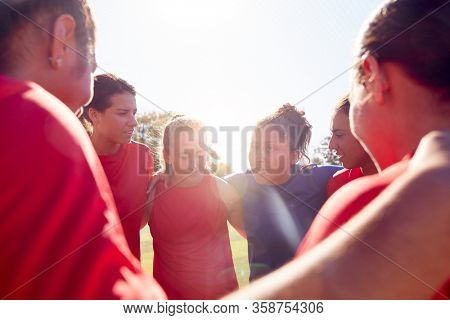 Manager In Huddle With Womens Football Team Giving Motivational Pep Talk Before Soccer Match