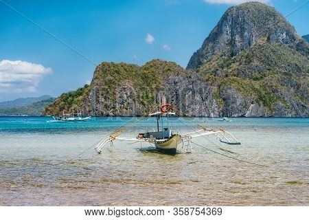 Palawan, Philippines. Traditional Filippino Banca Boat In Shallow Blue Tropical Lagoon In El Nido Ba