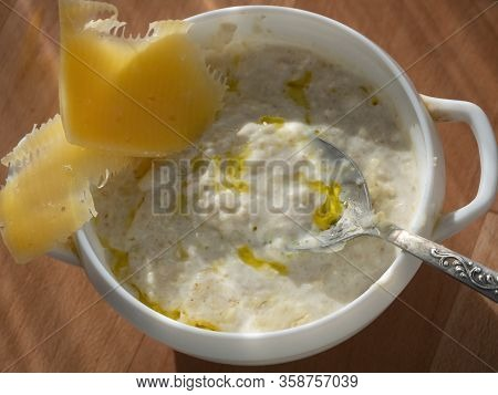 Oatmeal Porridge Is Put In A Deep Plate. Vegetable Oil Was Added To The Porridge. On The Edge Of The