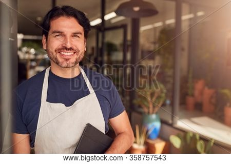 Portrait Of Male Owner Of Florists With Digital Tablet Standing In Doorway Surrounded By Plants