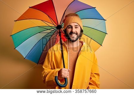 Young handsome man with beard wearing raincoat for rainy day holding colorful umbrella with a happy face standing and smiling with a confident smile showing teeth