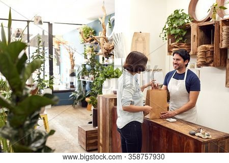 Male Sales Assistant In Florists Shop Serving Female Customer At Sales Desk