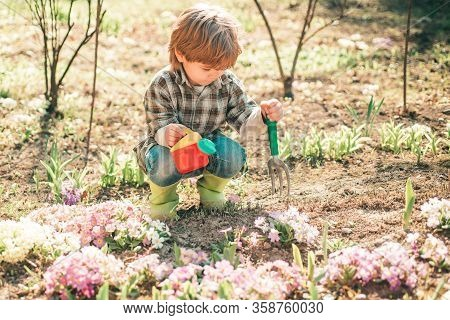 Child Play In Spring Garden. Earth Day. Lovely Child Walking In Spring Garden. Child Gardening In Th
