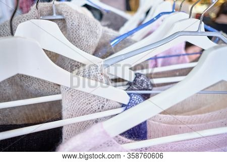 A Stand With Hangers Of Fashionable Lightweight Women Sweaters. Close Up.