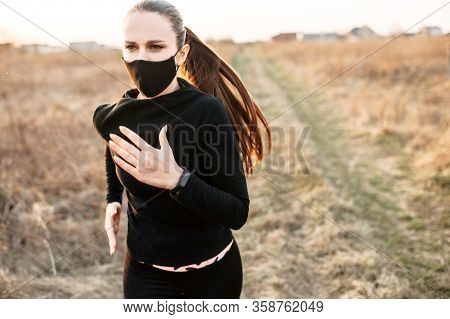 Sport During Quarantine, Self-isolation In The Countryside. A Young Athletic Woman Is Jogging On A D
