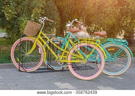 Two Yellow And Turqoise City Woman Bikes With Flowers In Park. Bright Lady Bicycles Vintage Style Wi