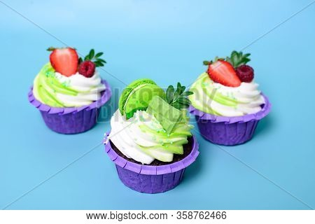 Three Cupcakes With Whipped Cream, Chocolate Bar, Strawberry , Decorated Macaroons On Blue Backgroun
