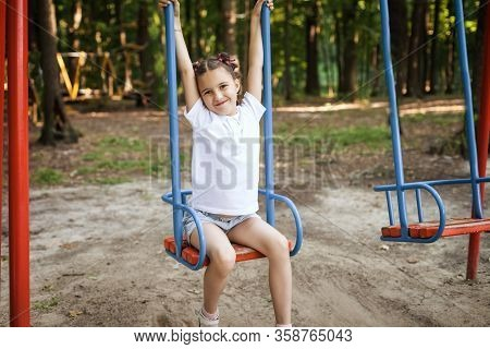 Cute Little Happy Girl Sitting On Swings At The Playground. Concept Of Summer, Childhood And Leisure