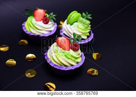 Cupcakes With Whipped Cream Decorated Chocolate Bar, Strawberry , Macaroons On Black Background. Pic