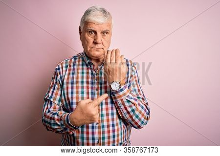 Senior handsome hoary man wearing casual colorful shirt over isolated pink background In hurry pointing to watch time, impatience, looking at the camera with relaxed expression