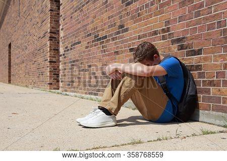 Depressed upset teenage student sitting outside school