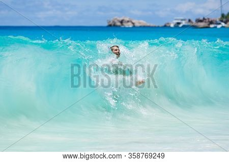 Teen Boy Enjoys His Vacation At Beach, Bathing In Splashing Waves Of The Turquoise Blue Ocean.