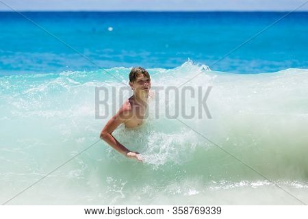 Young Teenager Boy Enjoys The Tropical Sea Waves At Beach.
