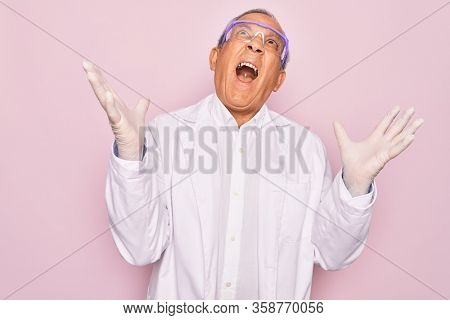 Senior grey-haired scientist man wearing glasses and coat over isolated pink background crazy and mad shouting and yelling with aggressive expression and arms raised. Frustration concept.