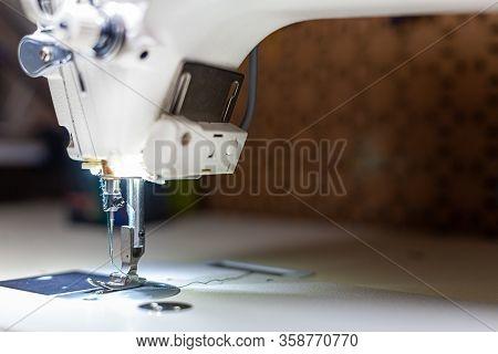 Sewing Machine Sews A Thin Transparent White Veil . Sewing Machine Foot Close Up. Sewing Process.