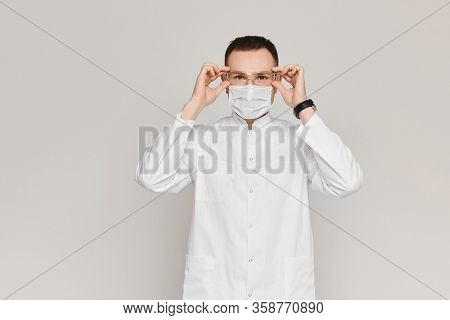 Handsome Dentist Or Doctor Wears A White Medical Gown, Face Mask And Protective Glasses On Grey Back