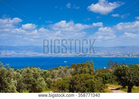 Summer Seascape On Cypus. View To The Bay With Green Grove In Front And Blue Clouded Sky. View From