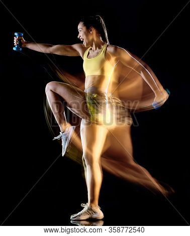 one mixed race woman exercising fitness exercises isolated on black background with lightpainting effect multiple exposures