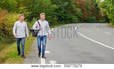 Free Way To Travel. Travel And Hitch-hiking. Twins Walking Along Road. Hitch Hiking Empty Road. Trav