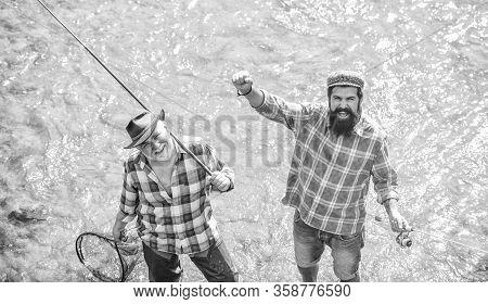 Summer Leisure. Fishermen Fishing Equipment. Hobby Sport Activity. Fishermen Friends Stand In River.