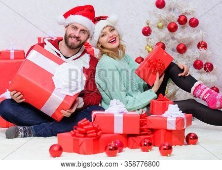 Couple In Love Enjoy Christmas Holiday Celebration. Woman And Bearded Man Wear Santa Claus Hat Chris