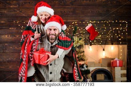 Man And Woman Santa Claus Hats Cheerful Celebrating New Year. Merry Christmas. Guy Piggybacking Girl