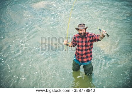 Fisher Have Fish And Long Rod. Man Relaxing And Fishing On River. Happy Bearded Fisher In Water. Hav