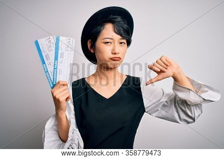 Young beautiful chinese tourist woman holding boarding pass airlane over white background with angry face, negative sign showing dislike with thumbs down, rejection concept