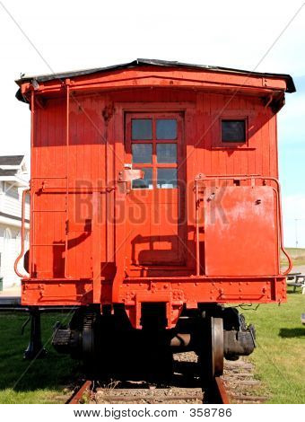 vintage caboose sitting in a public park. poster