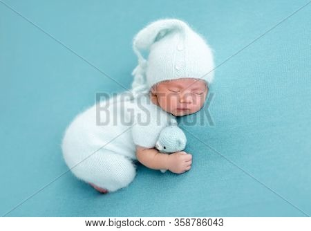 Cute sleeping newborn in knitted blue suit