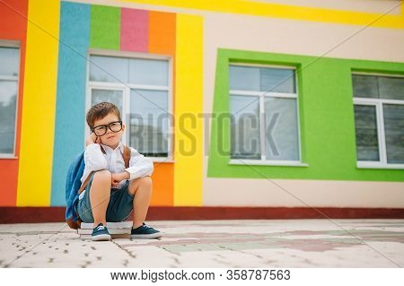 Sad Little Boy Outside Of School. Sad Schoolboy With Books Near A Modern School. School Concept. Bac