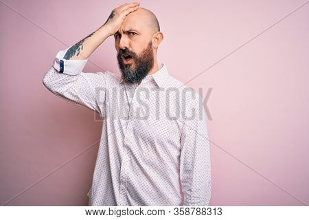 Handsome bald man with beard wearing elegant shirt over isolated pink background surprised with hand on head for mistake, remember error. Forgot, bad memory concept.