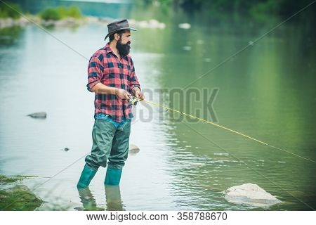 Fly Fish Hobby Of Man In Checkered Shirt. Sports Fishing. Fisher Have Long Rod. Nice Day. Fishing In