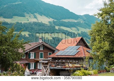 Beautiful Traditional Wooden House In The Alpine Village, Switzerland. House Decorated With Flowers,
