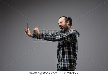 Bearded Man In Checked Shirt Menacingly And Aggressively Screaming At The Phone And Showing Clenched
