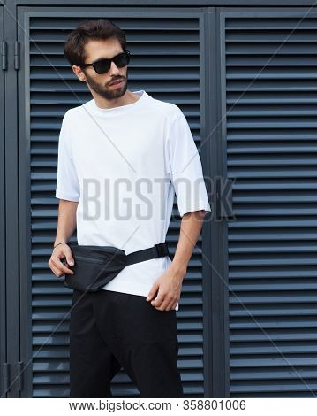 Fanny Pack, Bum Bag. Mens Street Youth Fashion. Young Hipster Man In Sunglasses With A Beard Posing