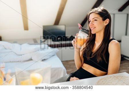 Woman In Sportswear Drinking Sweet Orange Amino Acid Powder Smoothie After Home Workout.keto Supplem