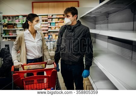 Couple Wearing Masks And Gloves Buying Groceries/supplies In Supermarket With Sold Out Products.food